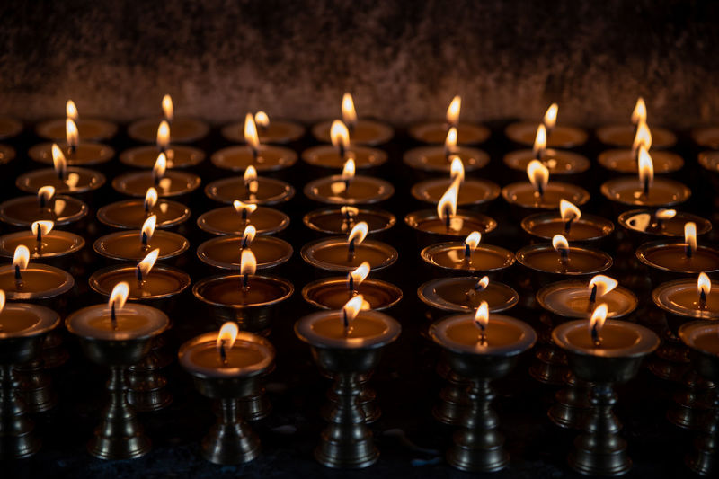 Close-up of lit candles in temple