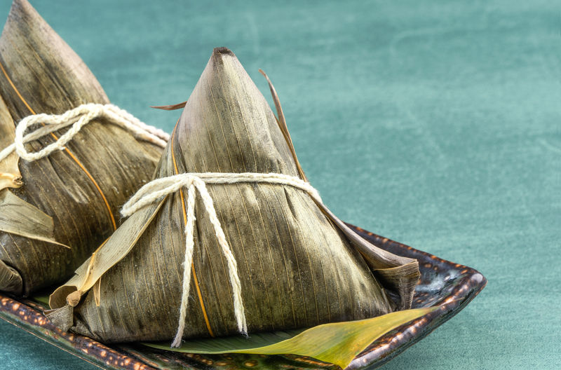 Close up, copy space, famous chinese food in dragon boat (duan wu) festival, steamed rice dumplings pyramidal shaped wrapped by bamboo leaves made by sticky rice raw ingredients Food And Drink Close-up Zongzi Rice Dumpling  Taiwan Dragon Boat Festival Duanwu Chinese Food Gourmet Cuisine Bamboo Leaves Green Backgrounds Tamale Holiday Tradition Traditional Asian  ASIA Delicious Handmade Recipe Tasty Eating Delicacy Closeup Copyspace Double Fifth Celebration Glutinous Rice Sticky Peanut Meat Dry Shrimp Texture Plate Serve Oriental Wrapped Ingredient Meal Summer China
