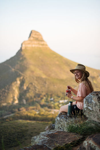 Woman sitting on rock against mountain against sky