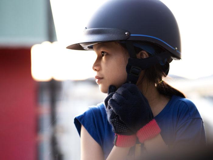 Close-up of girl wearing helmet looking away