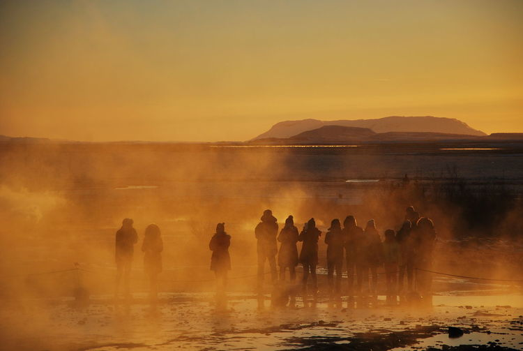 Silhouette people standing by hot spring against sky during sunset