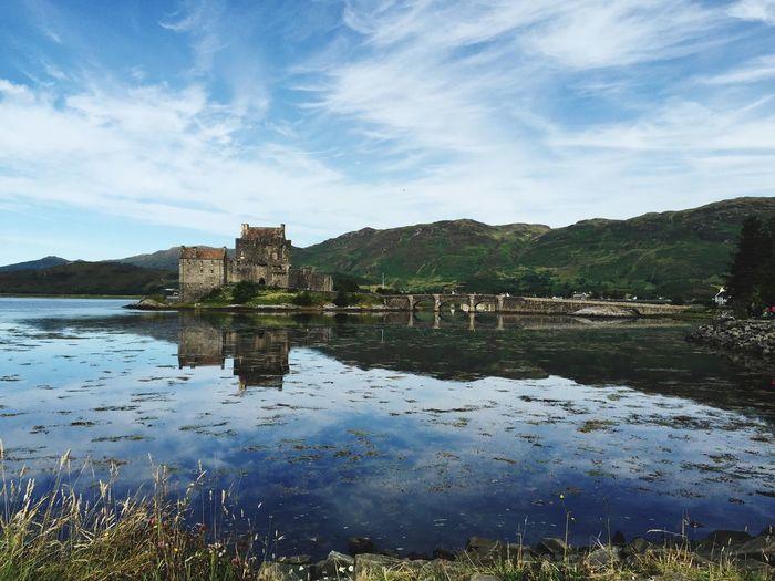 Eilean Donan Castle By Lake Against Sky