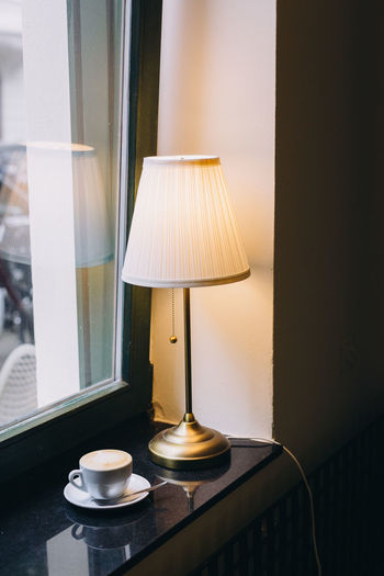 Close-up of illuminated lamp on table at home