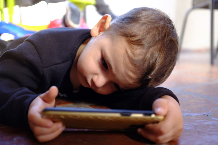 Rear view of boy using mobile phone