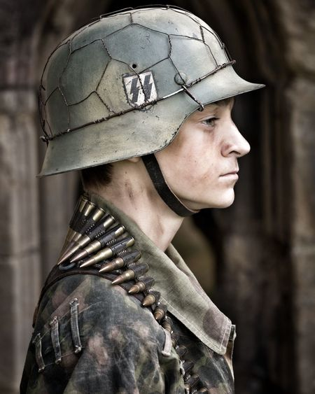 Profile View Of Young Soldier Wearing Helmet And Bullets