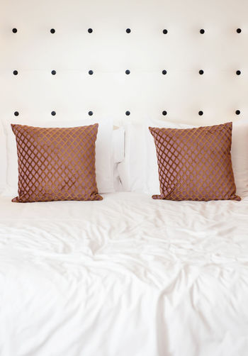 Cushions And Pillows On Bed Against Wall At Home
