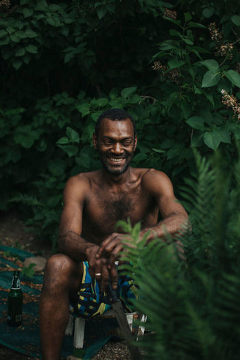 Portrait of shirtless man sitting by plants