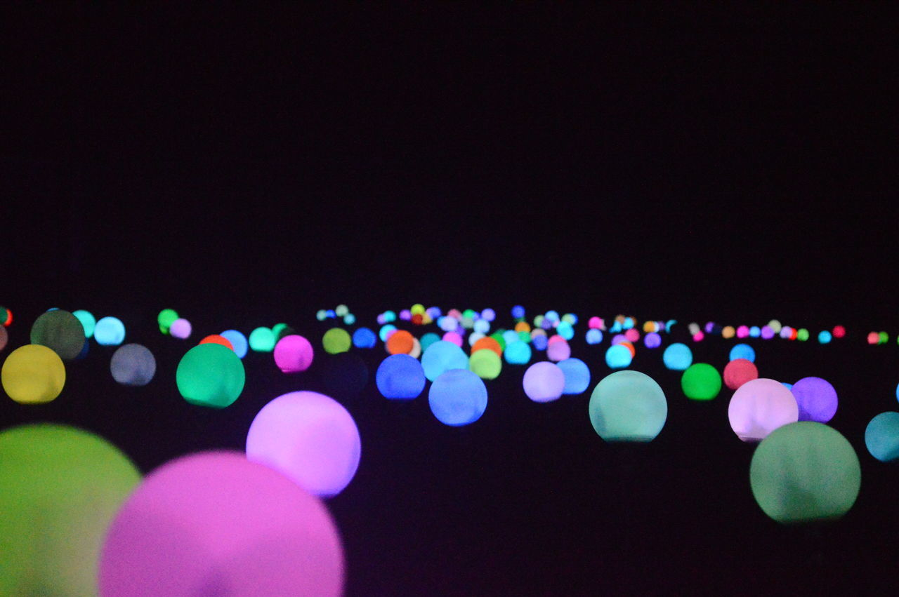 Colorful defocused lights against black background