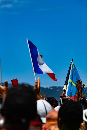 People with flags against clear blue sky