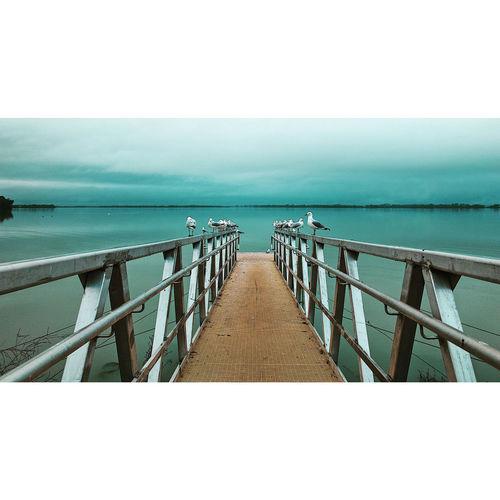 Empty pier on sea against clear sky