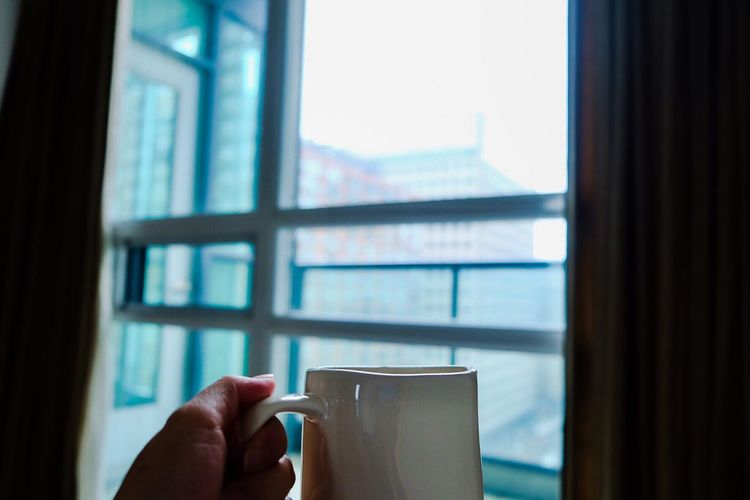 City life Apartment Buildings Apartment Condo Living City Life Condominium Coffee Break Coffee Cup Hand Window Holding Lifestyles Home Interior Focus On Foreground Cup