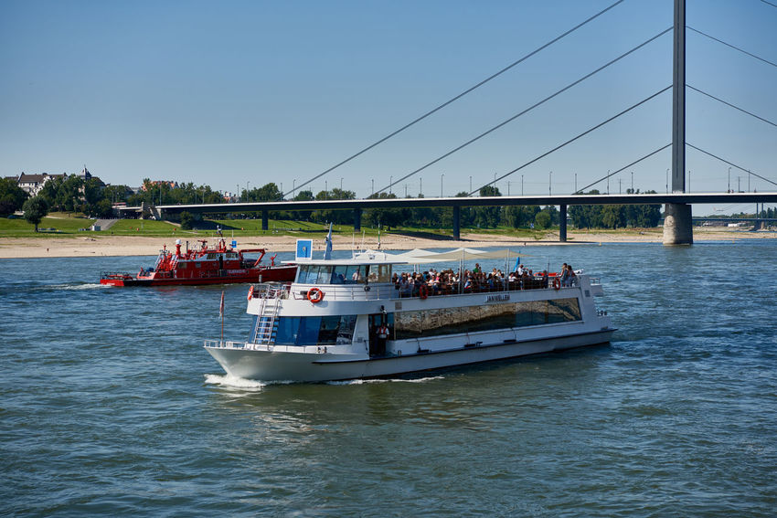 DUESSELDORF, GERMANY - AUGUST 17, 2016: A sightseeing and fire patrol boat cross their ways on river Rhine near Oberkasseler bridge Altstadt Atmosphere Bar Blu Sky City Life City Street Daytime Düsseldof High Resolution Lifestyles NRW Outdoors People R Relaxing Restaurant Rheinland-Pfalz  Rhine Promna S Shopping Tourism Travel Destinaton