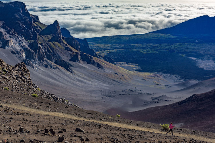 High angle view of woman walking at haleakala crater against cloudy sky