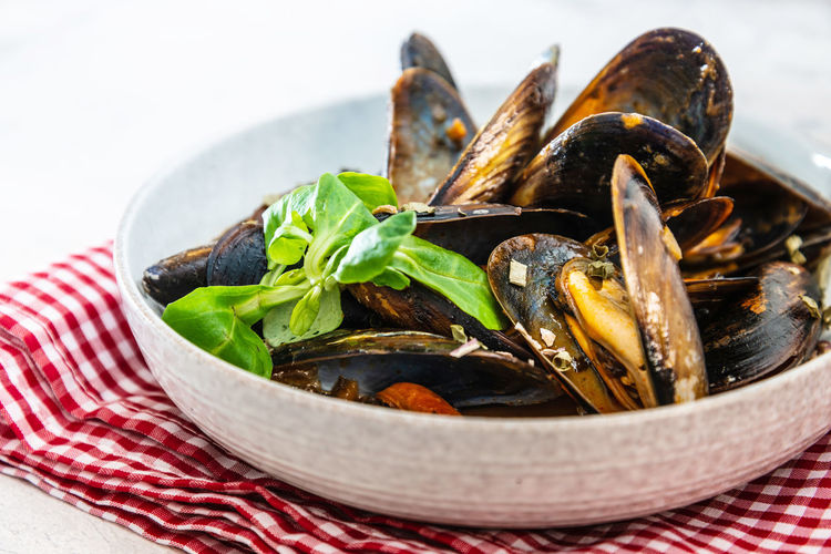 Close-up of mussels served in bowl on table against white background