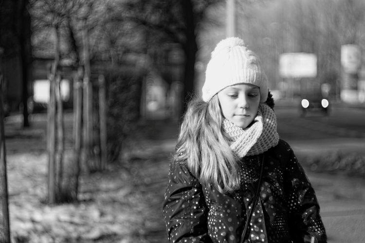 Girl wearing warm clothing while walking on footpath