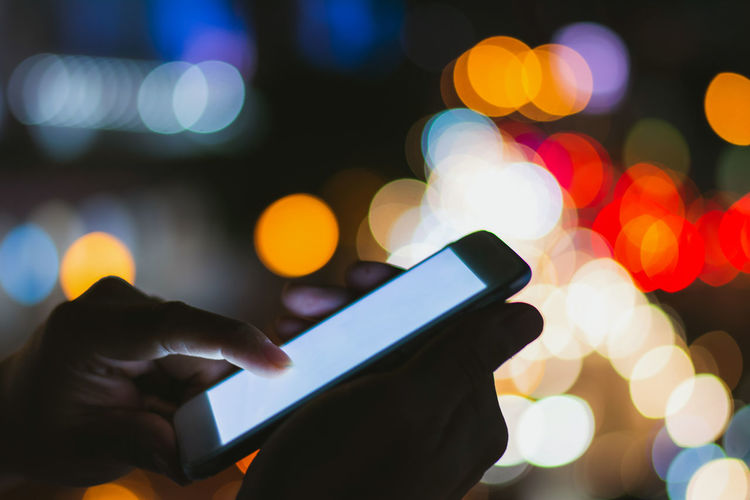 Cropped hands of person using phone against defocused lights at night