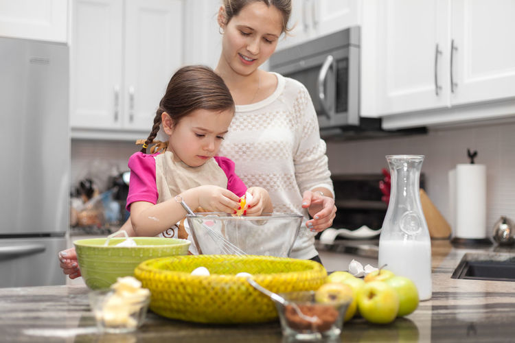 Happy family in the kitchen, mother and daughter cooking apple pie, breaking eggs Apron Cooking Family Happy Helping Home Laughing Activity Apple Pie Bake Childhood Dough Eggs Enjoying Life Flour Food Healthy Kitchen Lifestyles Little Helper Milk Mom And Daughter Parent Portrait Top View