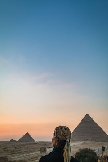 Sky Nature Outdoors Pyramids Egypt Desert Travel Tourism Destination Beautiful Ancient Structure Ruins Giza Cairo Sphinx Real People One Person Lifestyles Leisure Activity Sunset Women Scenics - Nature Adult Copy Space Standing Portrait Architecture Clear Sky Beauty In Nature Land Clothing Arid Climate Climate Looking At View It's About The Journey 2018 In One Photograph