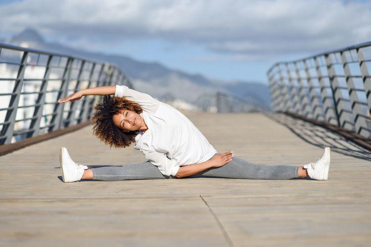 Woman Stretching Legs On Boardwalk Against Sky