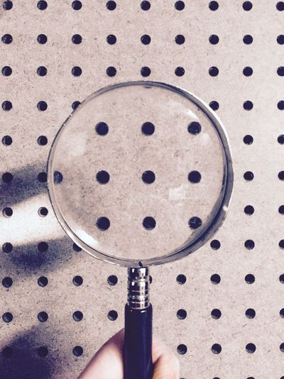 Cropped Hand Holding Magnifying Glass In Front Of Patterned Wall