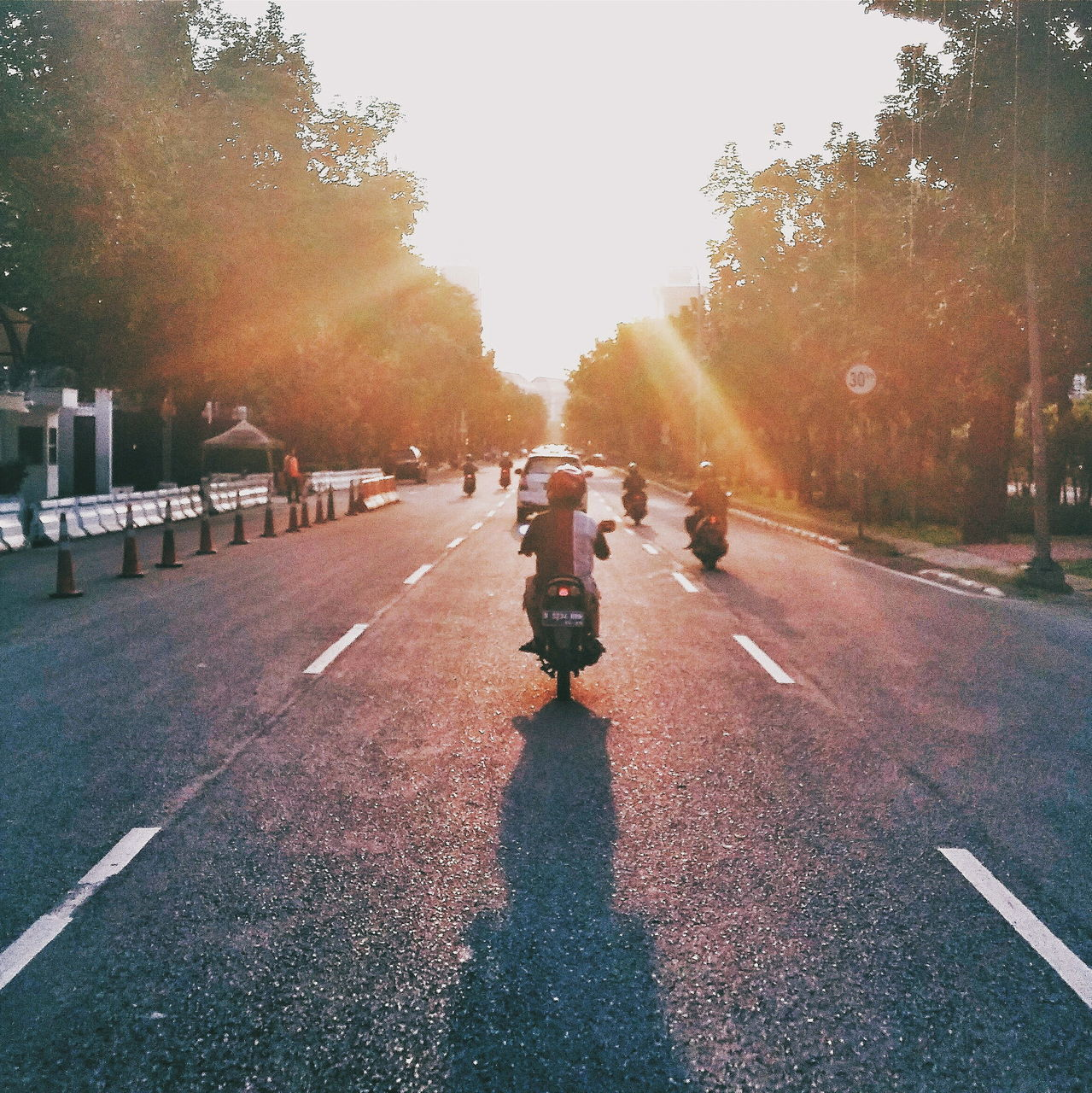 Rear View Of Man Riding Motorcycle On Street Against Sky During Sunset
