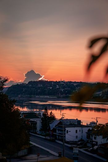 Sunset over Chicoutimi Mountain Tree Sunset City Reflection Sky Architecture Mountain Range Dramatic Sky Romantic Sky Sky Only Aurora Polaris Cloudscape Moody Sky Atmospheric Mood Residential Structure Storm Cloud Cityscape Capture Tomorrow