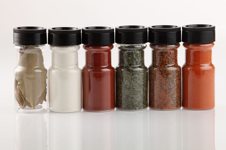 Close-Up Of Spices In Bottles Against White Background