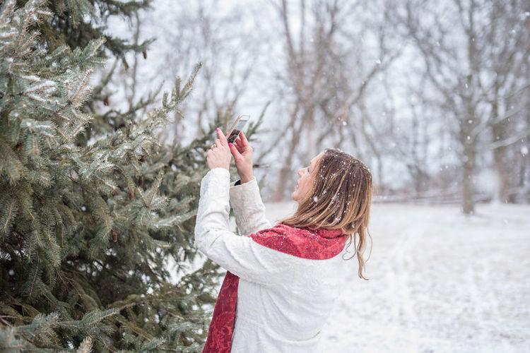 Woman photographing christmas tree during snowfall