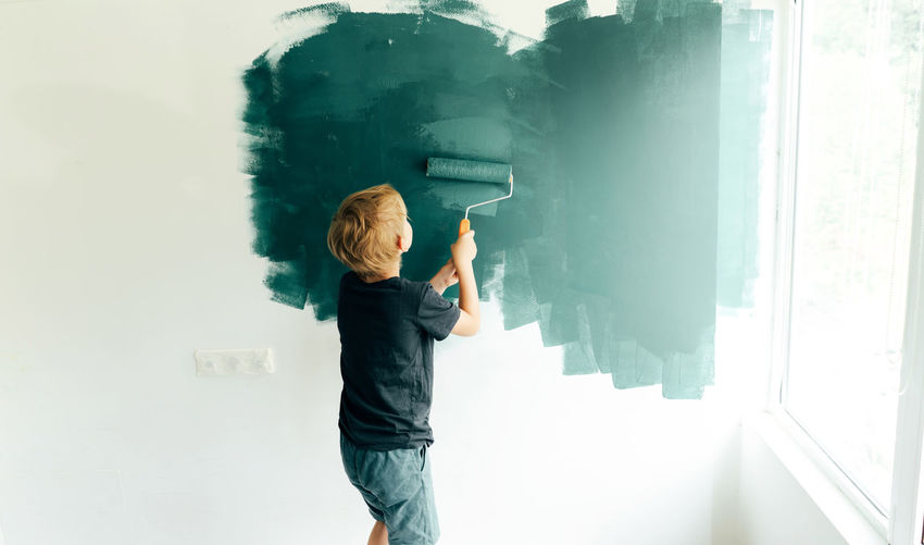 Side view of boy painting on wall at home