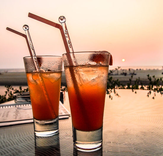 Close-up of drinks on table at sunset