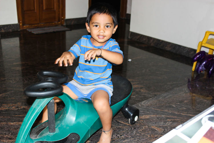 Portrait Of Smiling Boy Riding Tricycle At Home