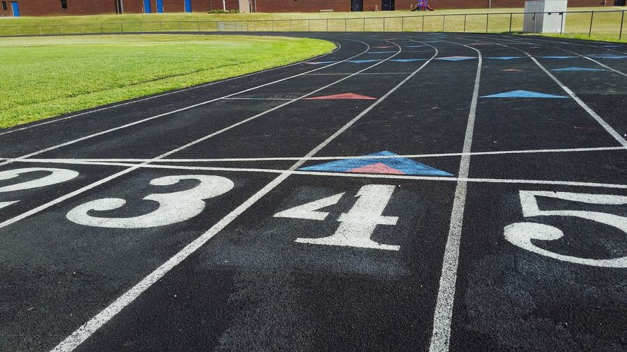 The Color Of Sport Track High Angle View Text Numbers Communication Outdoors Day No People The Way Forward Diminishing Perspective Focus On Foreground Sport Competitive Sport Guidance Direction Guidelines The EyeEm Collection