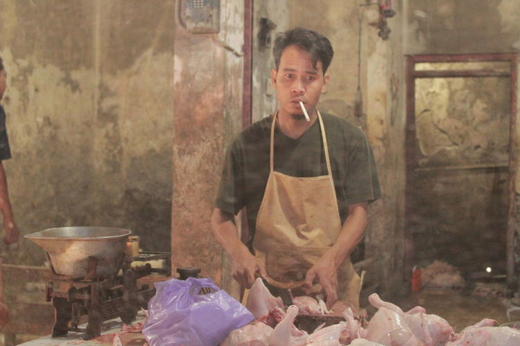 Portrait of butcher smoking cigarette while cutting meat