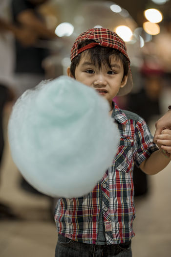 Portrait of cute boy holding cotton candy