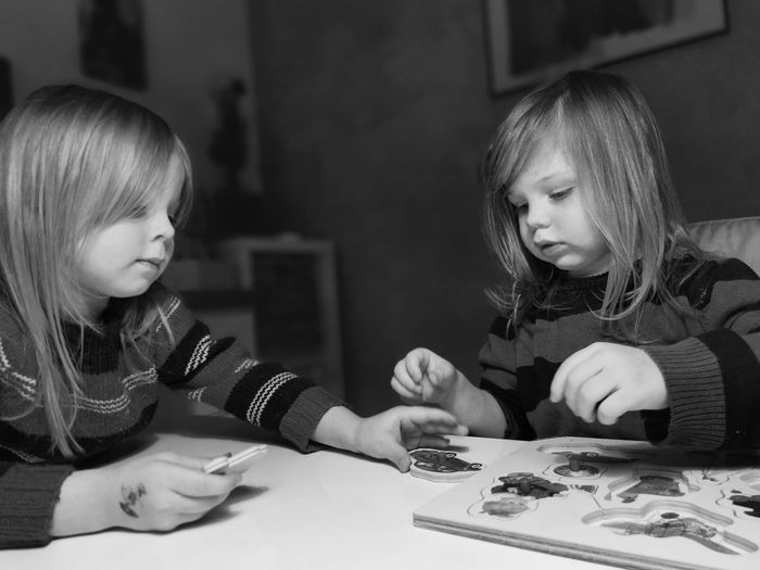 Happy girls with puzzle on table