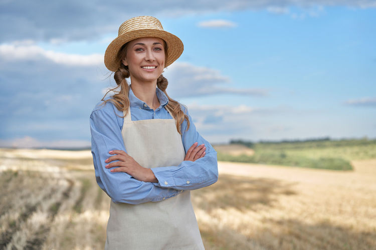 Portrait of smiling woman standing on field