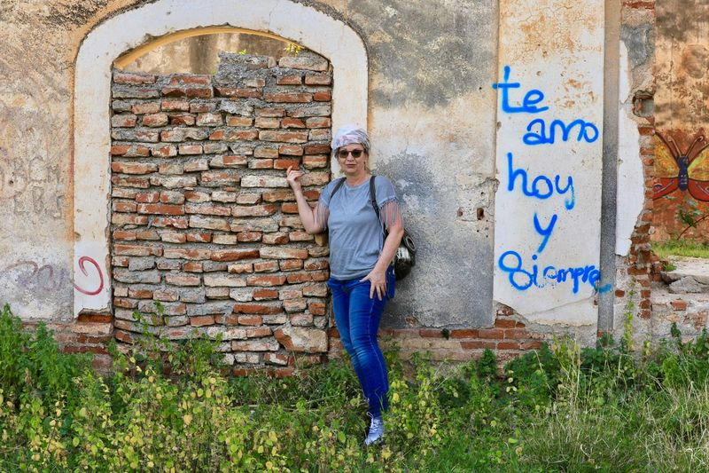 Portrait of woman standing against brick wall by text