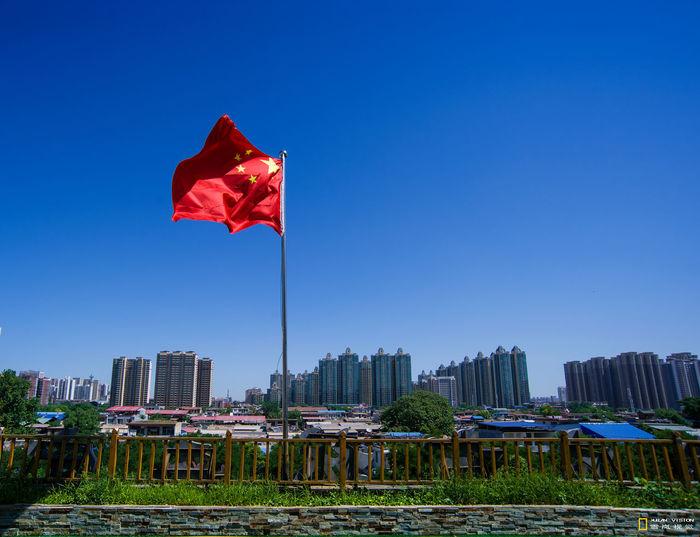 Flag against buildings in city against clear blue sky