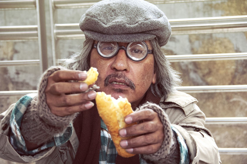 Homeless man on street and eating old bread. Adult Close-up Clothing Day Eating Food Food And Drink Freshness Front View Hat Headshot Healthy Eating Holding Hungry Leisure Activity Lifestyles Men One Person Portrait Real People Warm Clothing