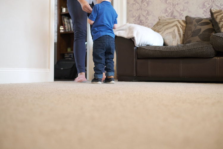 Low section of woman and boy standing on floor by sofa at home