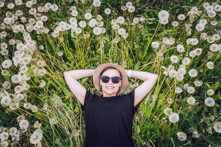 Directly above shot of smiling young woman lying down on dandelions