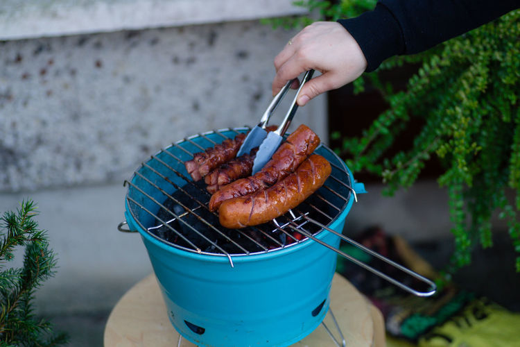 Cropped Hand Preparing Sausages On Barbecue Grill