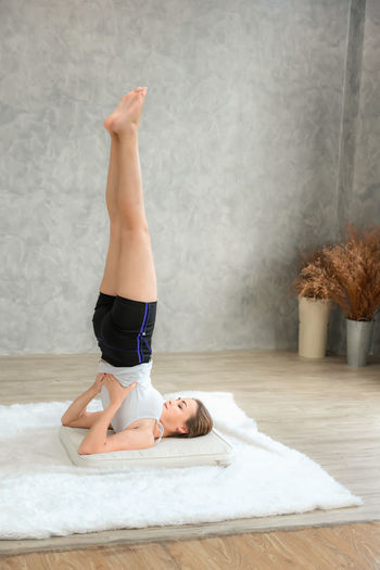 Portrait of attractive young woman practicing yoga indoors., Healthy and yoga concept. Lying Down Lifestyles Full Length Relaxation Indoors  Young Adult One Person Real People Leisure Activity Young Women Healthy Lifestyle Balance Lying On Back Furniture Women Bed Stretching Day Human Arm Beautiful Woman Yoga Sport Healthy