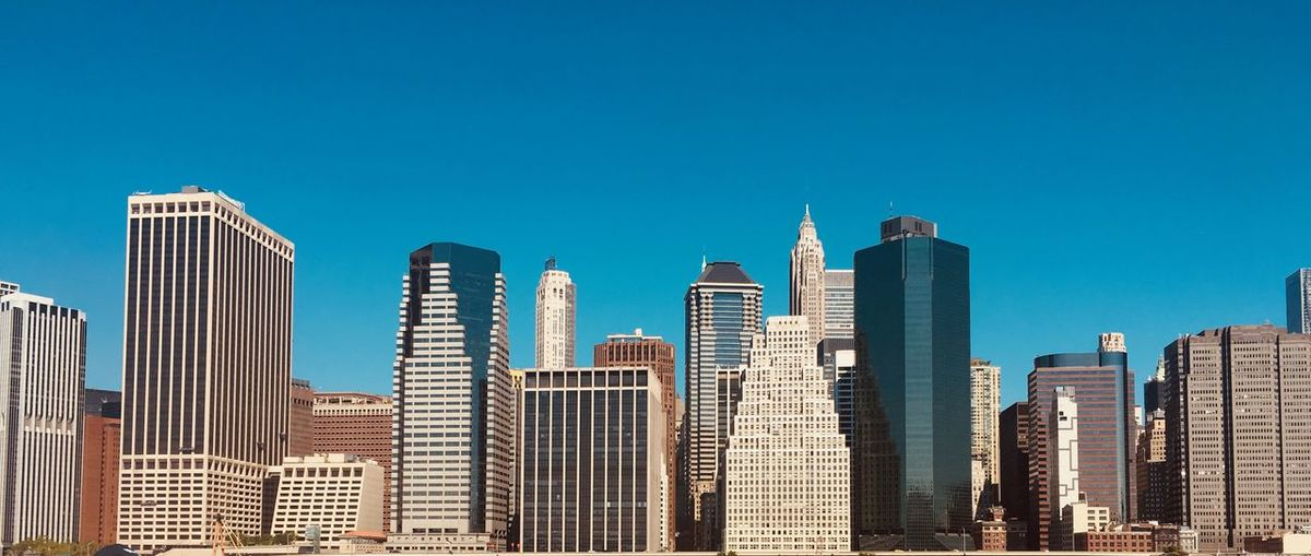 Skyscrapers in city against blue sky