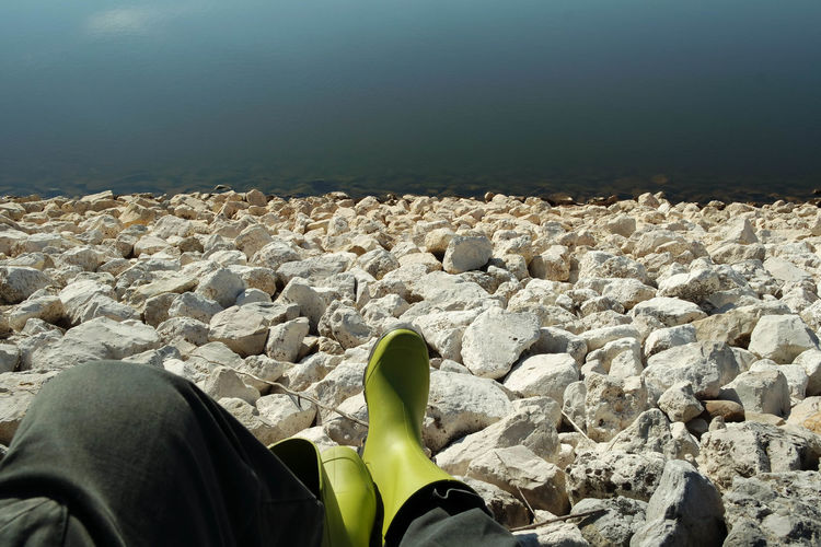 Abundance Beauty In Nature Close-up Day Footwear Lake Leisure Activity Lifestyles Low Section Nature Outdoors Part Of Pebble Person Personal Perspective Rock - Object Sky Standing Stone - Object Tranquil Scene Tranquility Unrecognizable Person