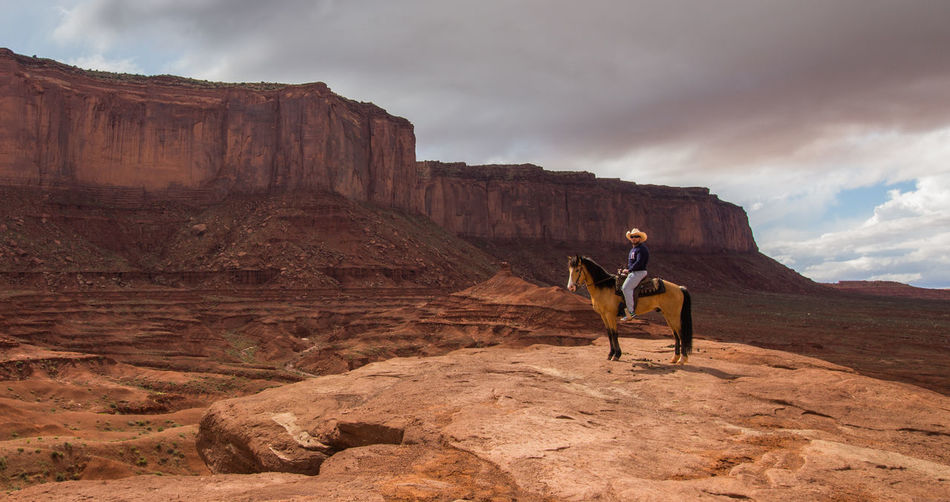 Man sitting on horse at cliff