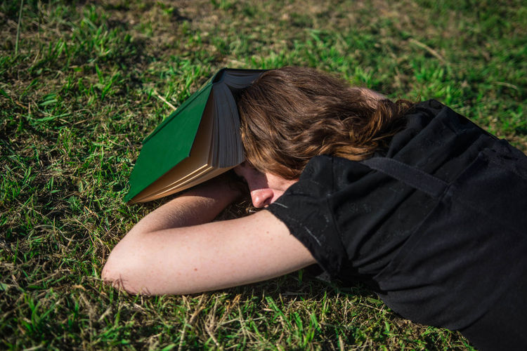 Young woman lying down in the grass with a book. One Person Nature White Woman Young Adult Portrait Curly Hair Freckles Black Dress Caucasian Candid Real People Smart Intelligent Intelligence Lifestyle Reading Green Nap Sleeping Lying Down Resting Relaxing Outdoors Tranquility Sunny Day Beautiful Book Grass Land Relaxation Day Boring Bored Boredom Studying Learning