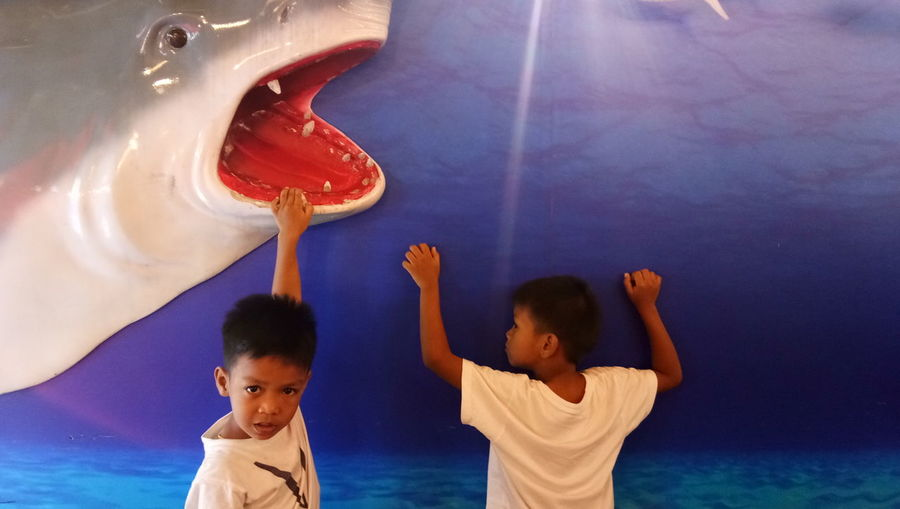 Cheerful boys playing with shark sculpture on wall