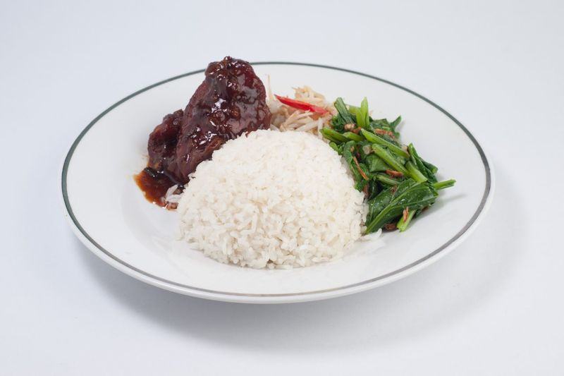 Rice with curry and salad served in plate against white background