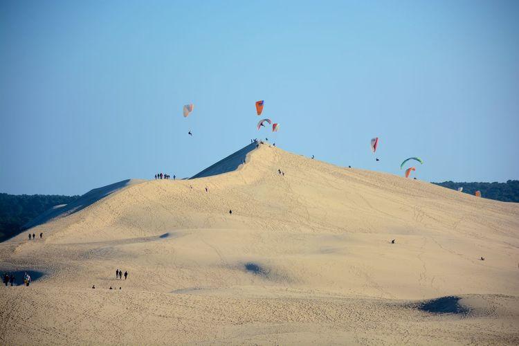 Kites flying over dune of pilat against clear sky